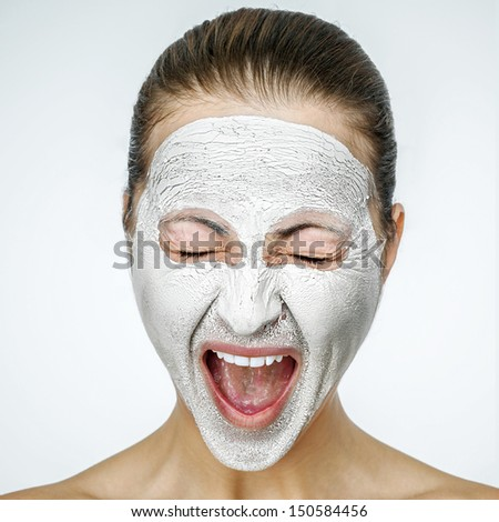 Young emotional woman with facial mask smirking