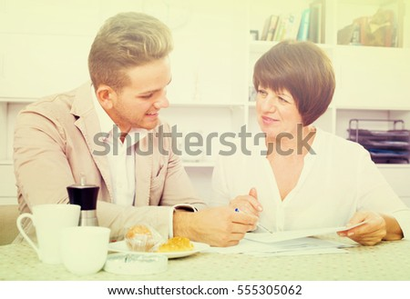 Young employee of company communicates with elderly woman behind a coffee squash