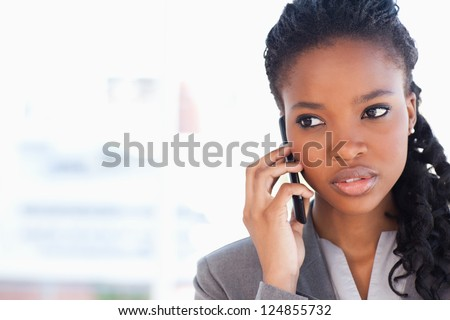 Young employee talking on the phone while looking towards the side - stock photo