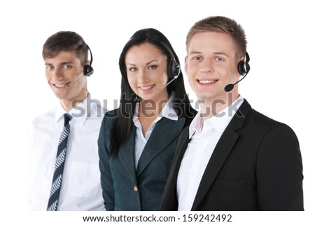 Young employee working with a headset and accompanied by his team. Standing isolated on white   - stock photo