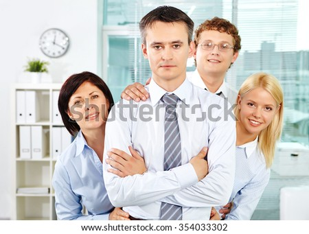 Young employees looking at camera from behind their business leader