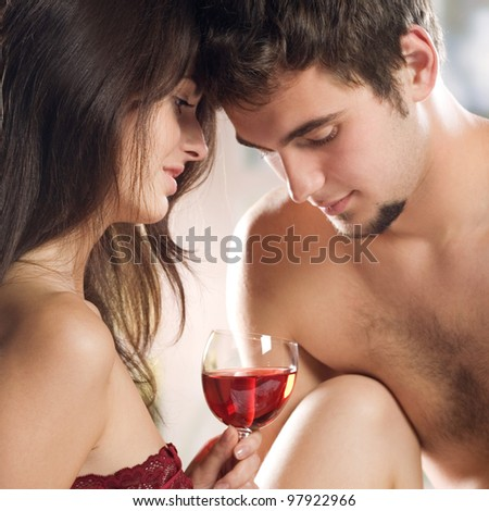 Young enamoured couple drinking red wine on the bed in bedroom - stock photo
