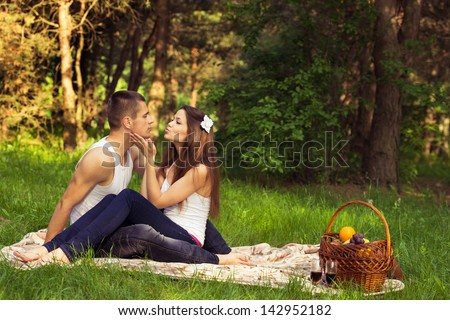 young enamoured couple on rest in park - stock photo