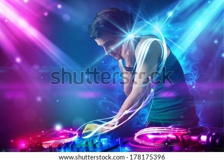 Young energetic Dj mixing music with powerful light effects - stock photo