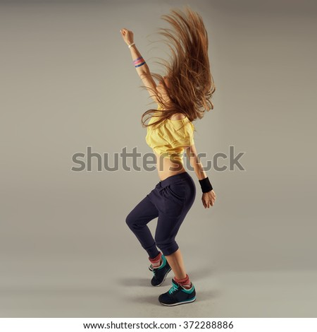 Young energetic woman with disheveled hair dancing  hip hop. Concept of lifestyle, sport and health. - stock photo