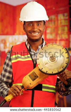Young engineer carpenter wearing helmet, square pattern flanel shirt with red safety vest, holding handheld electric sander tool smiling to camera - stock photo