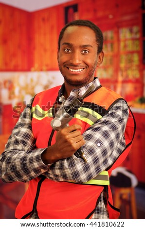 Young engineer carpenter wearing square pattern flanel shirt with red safety vest, holding handheld electric power tool smiling to camera - stock photo