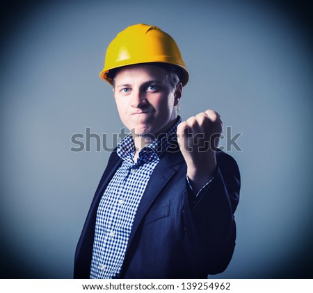 young engineer in a helmet  shows fist - stock photo