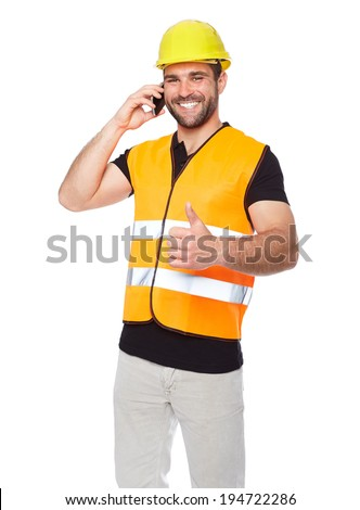 Young engineer in a reflective vest with yellow helmet calling by phone - stock photo