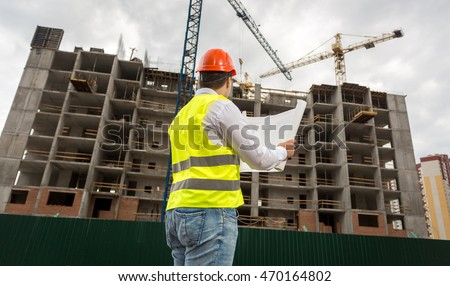 Young engineer on building site checking plans and blueprints