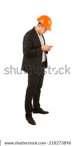 Young engineer or architect wearing a suit and hardhat standing sideways using his mobile phone to text a message or reading his incoming mail, isolated on white
