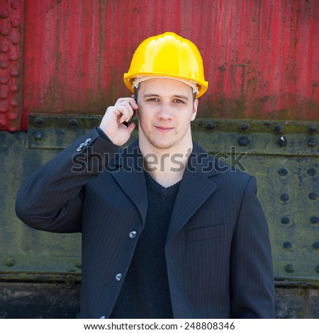 young engineer standing in front of old train - stock photo