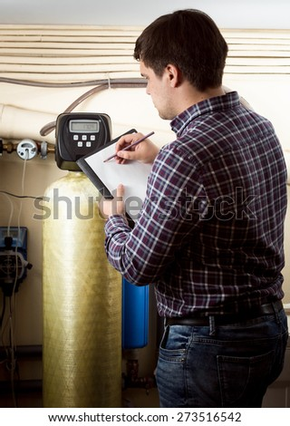 Young engineer writing down meter reading on industrial counters
