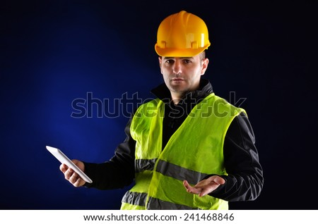 Young engineering with orange helmet working on a tablet pc - stock photo