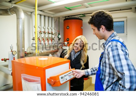 young engineers in heating boiler heating system with - stock photo
