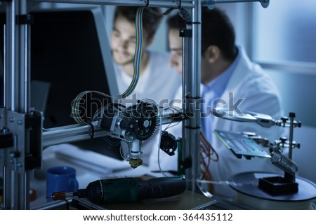 Young engineers working in the laboratory and using a computer, 3D printer on foreground, science and technology concept - stock photo