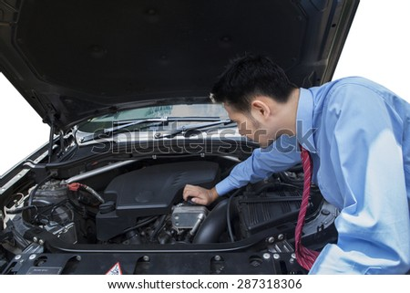 Young entrepreneur looking and checking the broken car machine