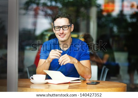 Young entrepreneur or student working in a cafe - stock photo