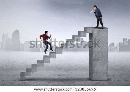 Young entrepreneur standing on the bar and calling his subordinate with a megaphone