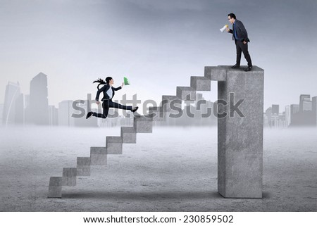 Young entrepreneur standing on the bar and using a megaphone to command his subordinate