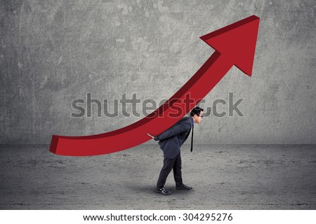 Young entrepreneur try to bring an upward chart, symbolizing business growth - stock photo