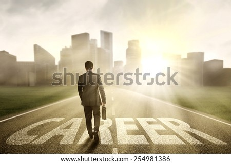 Young entrepreneur walking on the road while carrying briefcase to get bright career in the city - stock photo