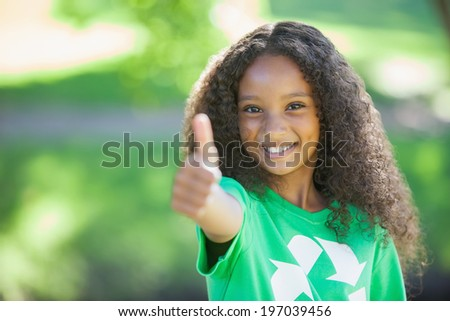 Young environmental activist smiling at the camera showing thumbs up on a sunny day - stock photo