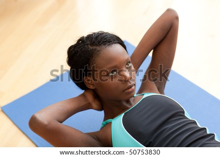 Young ethnic woman in gym clothes working out - stock photo