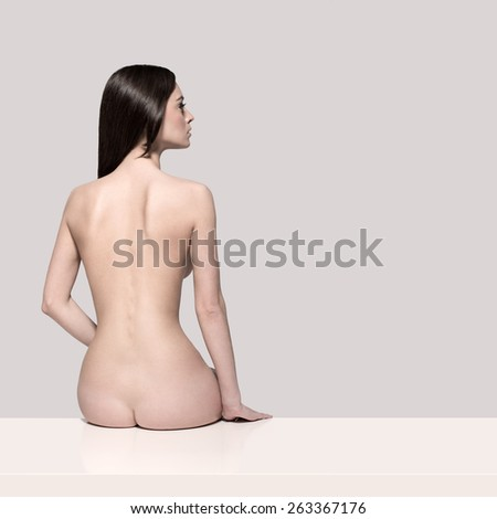 Young European fashion model woman with shiny healthy brunette hair, awesome gorgeous slim body and perfect skin sitting on the table nude in studio for bodycare and wellness advertisement, isolated - stock photo