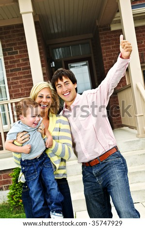 Young excited family celebrating in front of new home - stock photo