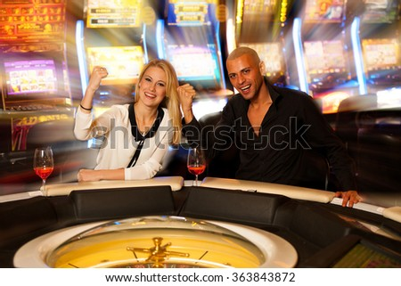 young excited happy couple playing roulette in casino betting and wining money - stock photo