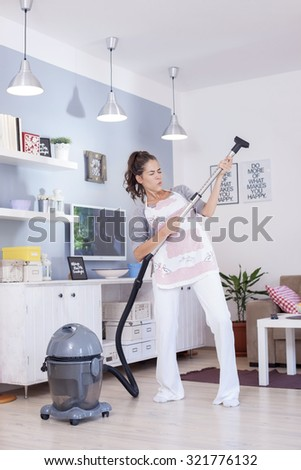 Young excited woman cleaning with a vacuum cleaner