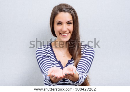 young excited woman holding her hand showing something on the open palm - stock photo
