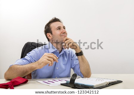 Young executive holding his chin on his hand and lost in happy thoughts at work. - stock photo