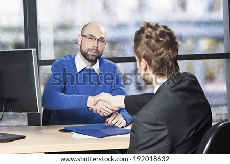 Young executive shaking hands to its employee in the office - stock photo