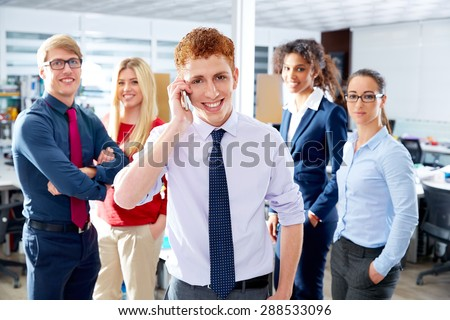 young executive talking phone in multi ethnic teamwork group as leader in office - stock photo