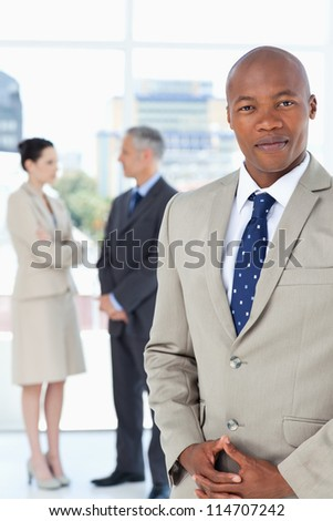 Young executive wearing a suit and crossing his hands with his team behind him - stock photo