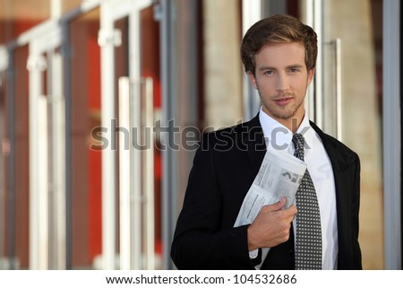 Young executive with newspaper - stock photo