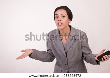Young executive woman dressed in grey and with a cellular demanding answers - stock photo