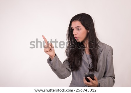 Young executive woman dressed in grey and with a cellular pointing out with her finger and her gaze towards the side - stock photo