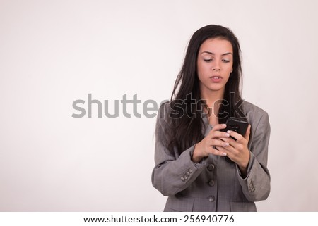 Young executive woman dressed in grey and with a cellular texting and looking down - stock photo