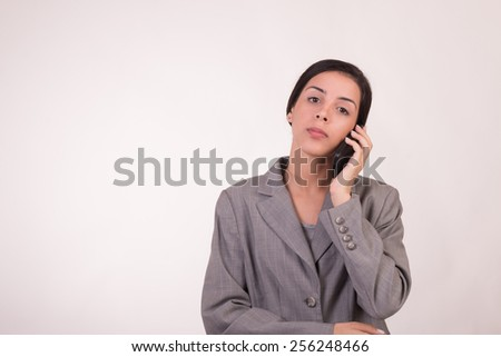 Young executive woman dressed in grey and with a cellular with her hands crossed and waiting for answers - stock photo