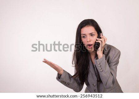 Young executive woman dressed in grey listening and screaming on her cell phone - stock photo