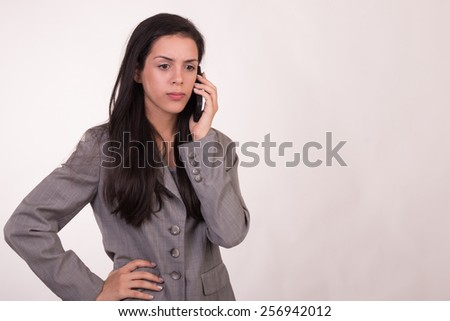Young executive woman dressed in grey listening by cellular her hands on her waist and looking forward - stock photo