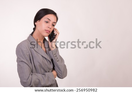 Young executive woman dressed in grey listening for her phone and hands crossed - stock photo
