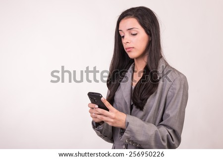 Young executive woman dressed in grey with a cellular and face of happiness - stock photo