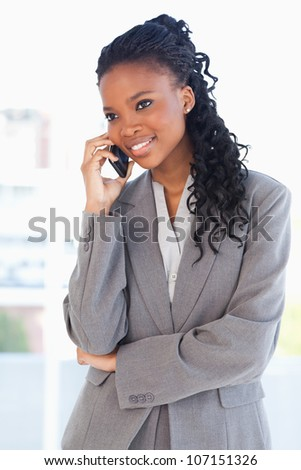 Young executive woman smiling and crossing her arms while talking on a phone