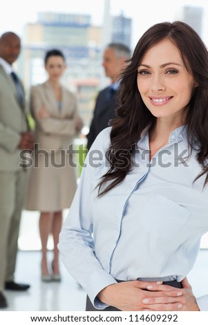 Young executive woman standing upright with her hands crossed on her hip - stock photo