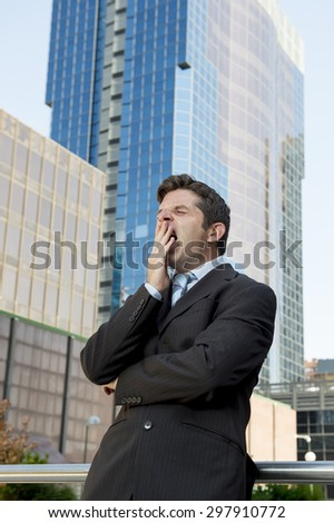 young exhausted and tired businessman standing yawning outdoors on street in front of business buildings at financial district looking destroyed in need of sleep  after long hours of work  - stock photo