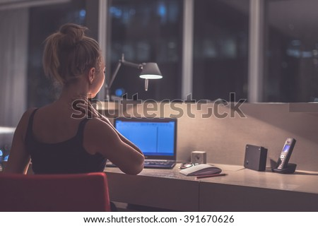 Young exhausted,depressed,concentrated woman sitting in her room or office with french windows  in the dark at the lamp.Studies late at night.Staying up late. Overworking.Feeling pain in the neck - stock photo